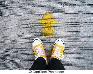Selfie feet wearing yellow sneakers in front of arrow on concrete road.
