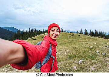 selfie image of a young smiling woman hiker with small backpack standing on a mountain slope.