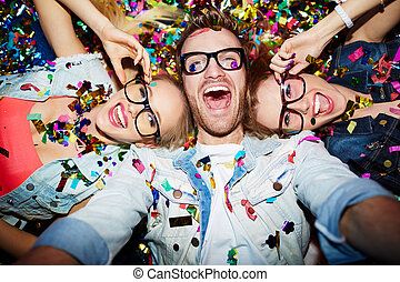 Selfie in nightclub - Cheerful friends lying on the floor in...