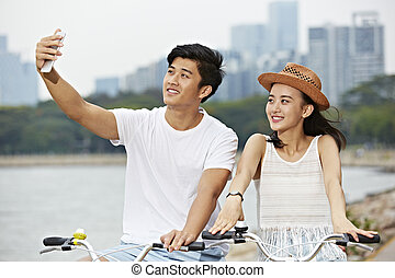 selfie, jovem, bicicleta, asiático, levando, montando, par