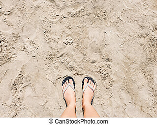 Selfie of feet in sandals shoes on beach sand background, top view