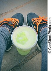 Selfie of sneakers with green vegetable smoothie.