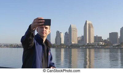 Young man shows a peace sign and makes a selfie - Selfie on...
