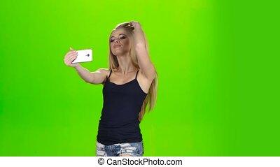 Selfie photo on the mobile phone makes blonde girl model