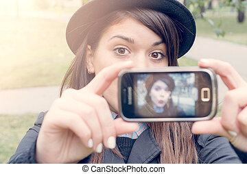 Selfie time - Beautiful young woman photographing herself...