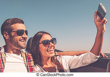 Selfie time! Three young happy people enjoying road trip in convertible and making selfie