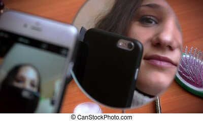 Selfie. Young beautiful woman making self portrait with a phone front of the mirror and smiling