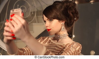 Selfie. Young teenage girl taking photo in golden dress and jewelry. Elegant lady in sequin dress posing by mirror with bulbs for makeup, in Luxury apartment at party.