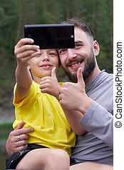 Selfies of father and son in summer on nature