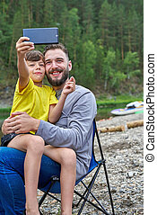 Selfies of father and son in summer on nature. Vertical frame