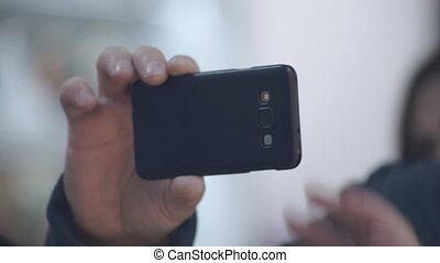 Selfies on iPhone - Men's hands hold the iPhone to take...