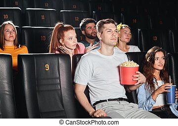 selfish tall guy eating popcorn loudly