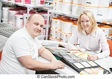 Seller and buyer selecting paint color - Assistant seller...