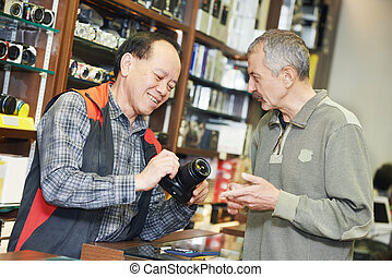 Seller demonstrating photo camera to buyer - Assistant...