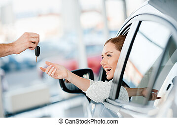 Seller giving key to happy young woman sitting in new car