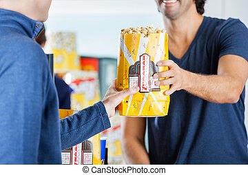Seller Giving Popcorn To Man At Concession Stand