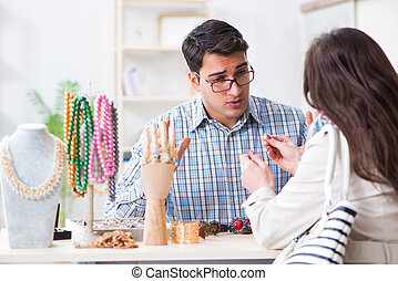 Seller giving price estimate to woman for jewelery