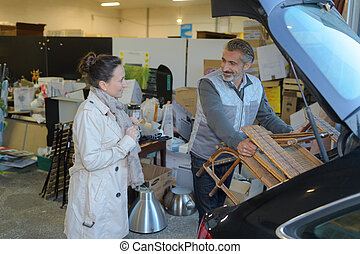 seller helping customer to load her purchases in her car