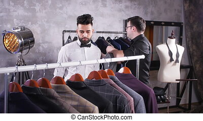 Seller in the costume shop helps the young man to choose a...