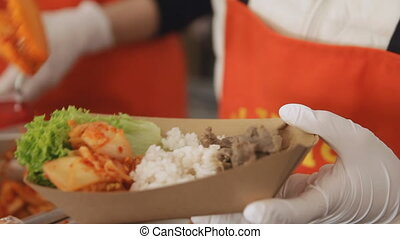 Seller is putting japanese food into a cardboard plate at...