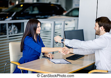 Seller male and customer female in the car retail office