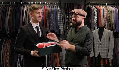 Seller man giving the shoes box to the male customer. Designer presenting shoes to a business man at the clothing store