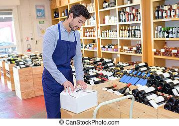 seller man wearing apron in wine store