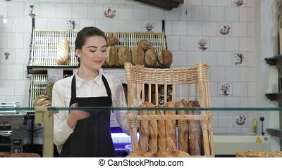 Seller near basket of baguettes