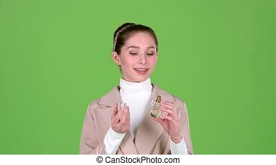 Seller of cosmetics advertises a pleasant fragrance of perfume. Green screen. Slow motion