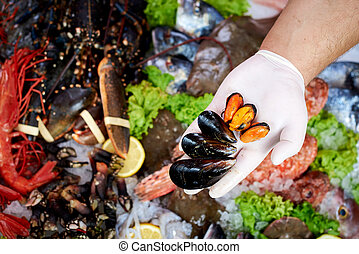 Seller presenting fresh mussels in fish store