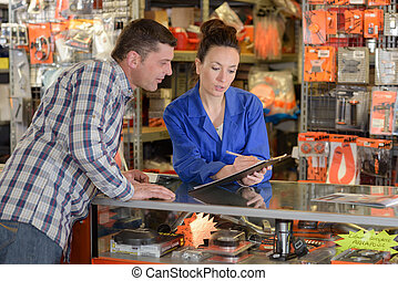 seller showing clipboard to customer in shop