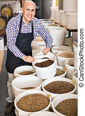 Mature glad smiling male seller taking bird seeds with scoop from bucket on market stall