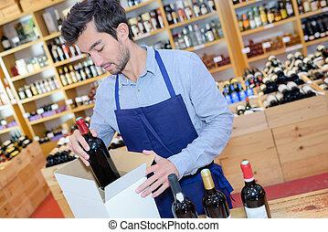 seller wearing apron preparing box with bottles in wine ...