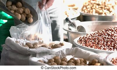 Selling walnuts at the bazaar. Varous kinds of nuts at market stall. Seller puts walnuts in plastic bag.