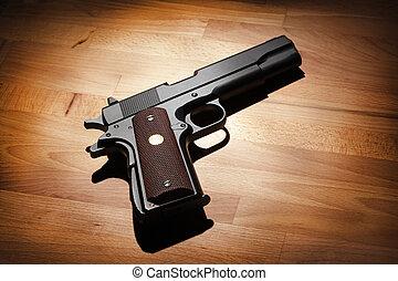 M1911 semi-automatic .45 caliber pistol on a wooden surface. Studio shot