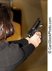 A picture taken over the shoulder of a young woman firing a semi-automatic handgun at a shooting range, showing the gun's recoil.