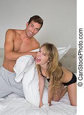 semi nude, young párosít, párna verekszik, ágyban