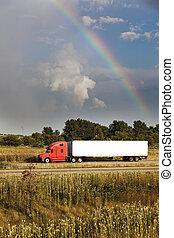 Semi truck driving under the rainbow