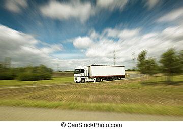 Semi truck - White truck on blurry asphalt under blue sky...