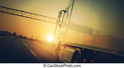 Semi Truck Riding On Highway At Sunset.