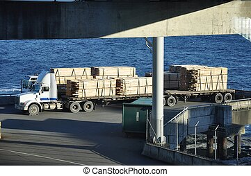 Two semi trucks loaded with lumber waiting to board the ferry.