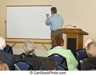 Seminar - Adult classroom with teacher writing on a dry-...