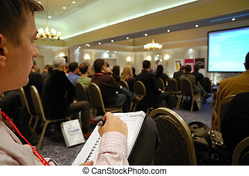 seminar - business man taking notes on seminar conference