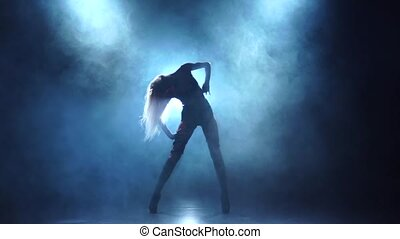 Seminude female dancer in leather lingerie. Smoky background, slow motion
