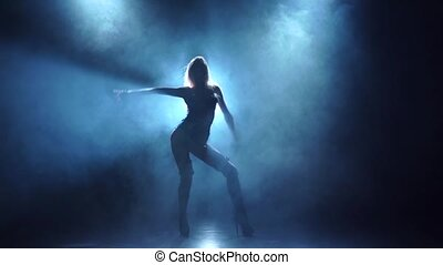 Seminude female dancer in swordbelt underclothes. Smoky background, slow motion