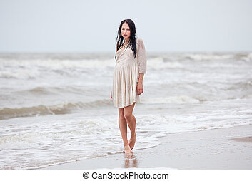 seminude woman in the cold sea waves - Beautiful young...