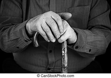 Semior's hands on cane - Old man hand's on wood cane in...