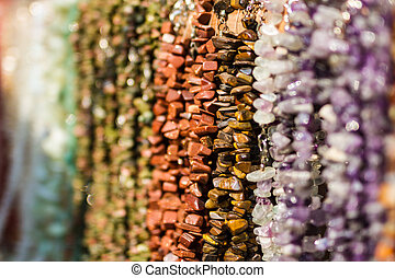 Background from multicolored semiprecious polished stones on jewellery market