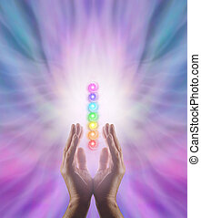 Male parallel hands facing upwards with white energy and the Seven Chakras floating between on a pink and blue ethereal energy formation background