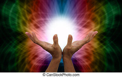 Healer's outstretched open hands with ball of white light between on a rainbow colored butterfly shaped energy formation background